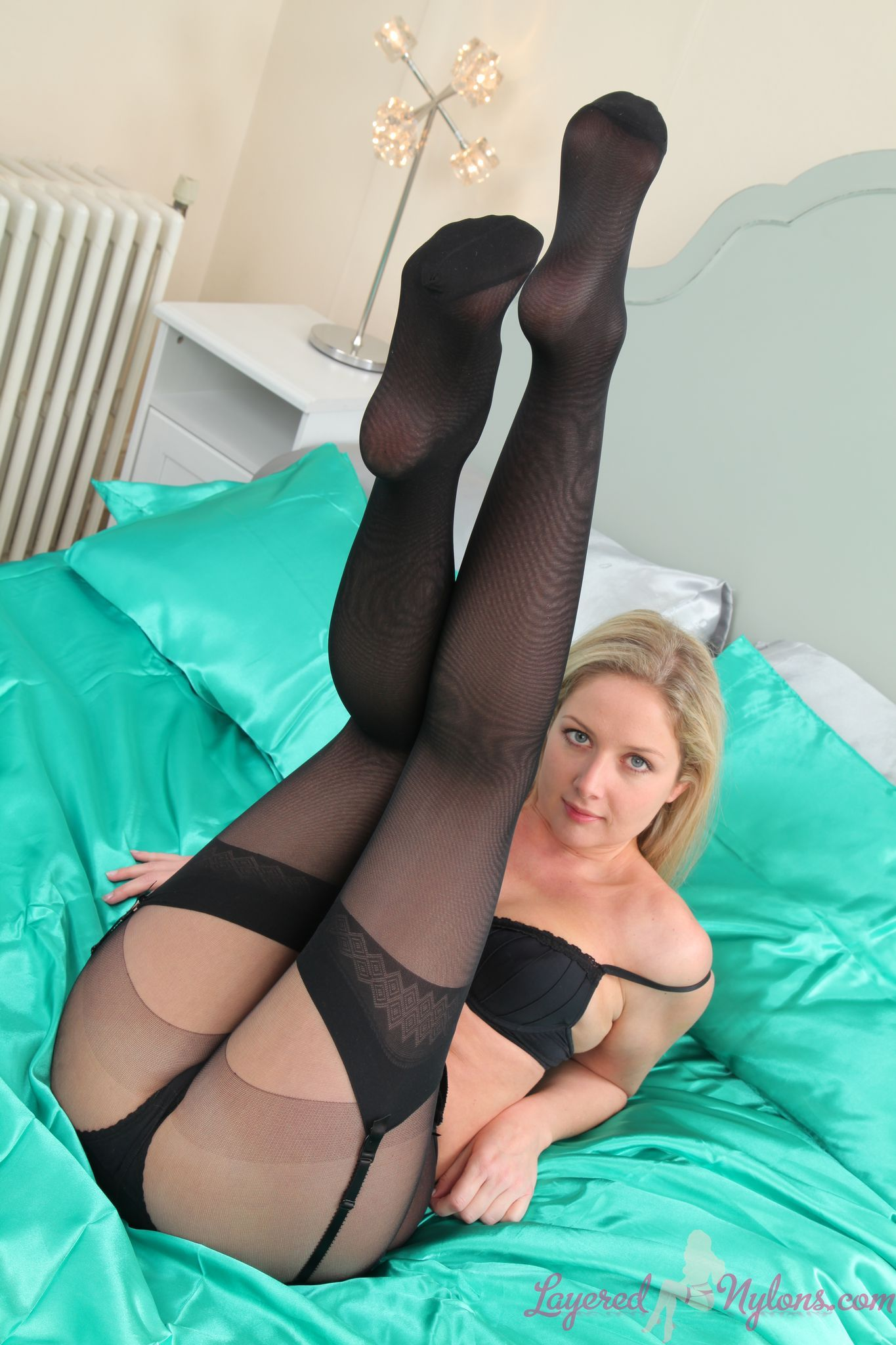 Sexy Blonde Model Teases In Black Pantyhose Over Stockings And Suspenders At Layered-Nylons