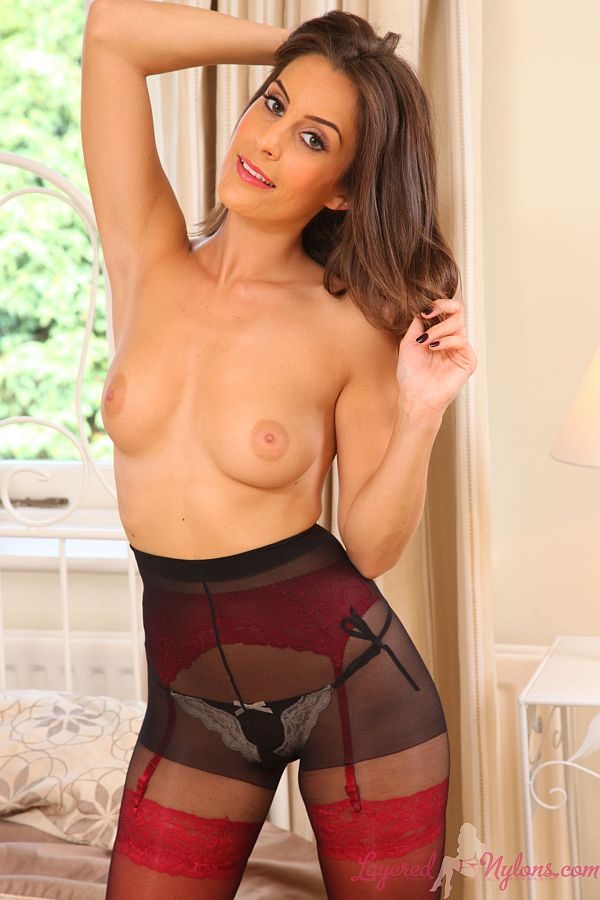 Sexy Brunette Teasing In Layers Of Red Lingerie And Black Nylon Pantyhose At Layered-Nylons