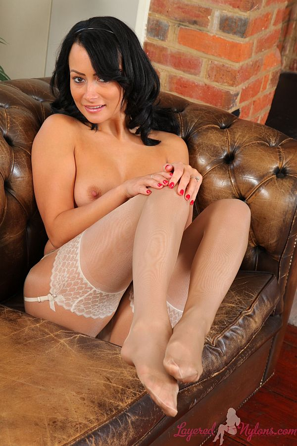 Raven Haired Model Teasing In Layers Of Shiny Nylon Pantyhose, Stockings and Suspenders At Layered-Nylons