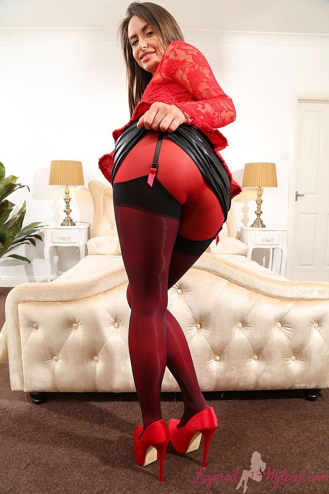 Brunette Babe Teases In Leather Skirt, Red Nylon Pantyhose, Black Suspenders and Stockings At Layered-Nylons