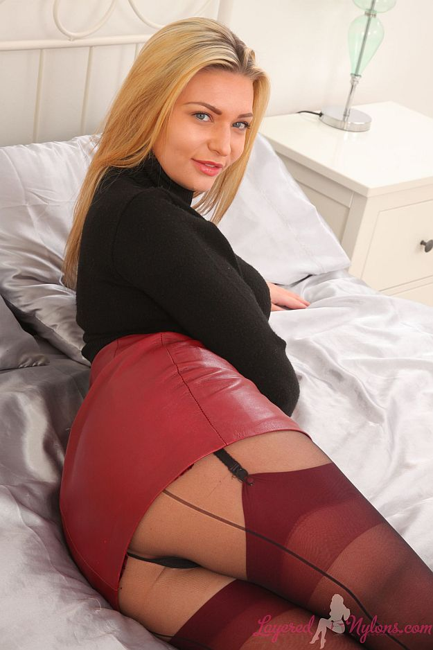Busty Blonde Teases In Black Suspenders, Nylon Pantyhose and Red Stockings at Layered-Nylons